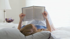 Woman reading in bed Stock Footage