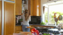 Woman preparing meal in kitchen Stock Footage
