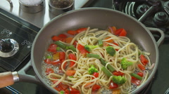 Pasta primavera cooking on stove Stock Footage