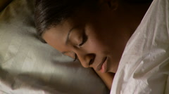 Portrait of young woman sleeping in bed - stock footage