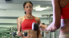 Young woman lifting weights at gym - stock footage