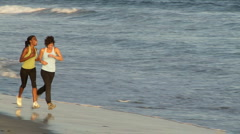 Stock Video Footage of Two young women running along shore line at sunset