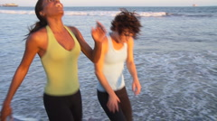 Two young women catching their breath at end of run on the beach - stock footage