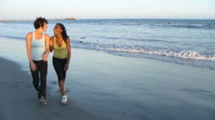 Two young women walking along seashore after a run Stock Footage