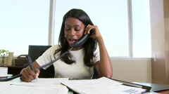Young businesswoman working at desk and answering phone in the office - stock footage