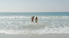 Young couple splashing and playing in the ocean at the beach Stock Footage