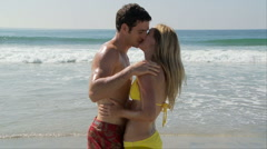 Young couple kissing at shoreline of ocean Stock Footage