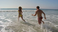 Young running in ocean and kissing Stock Footage