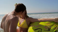 Young couple kissing at oceans edge with scarf blowing in breeze - stock footage