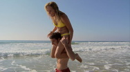 Young couple at beach giving piggy back rides Stock Footage