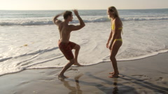 Young couple being goofy and having fun at beach - stock footage