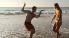 Young couple being goofy and having fun at beach dancing Stock Footage
