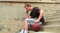 Young man with basketball talking on cell phone - stock footage