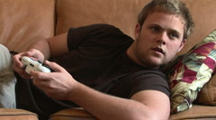 Young man on couch playing video game Stock Footage