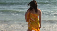 Young woman with sarong standing by ocean with wind blowing Stock Footage