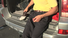 Young male golfer taking off golf shoes Stock Footage