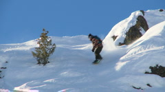 Male snowboarder carving through steep terrain - stock footage