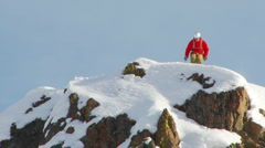 SLOW MOTION - Male skier jumping off fifteen foot rock into powder - stock footage