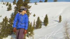 Female snowboarder smiling and throwing hands in the air Stock Footage