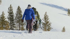 Male and female snowboarders hike through back-country powder Stock Footage
