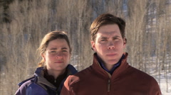 Couple outdoors in snow making eye contact with camera Stock Footage