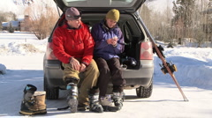 Couple sitting at the back of car talking on cell phone and putting on ski boots Stock Footage