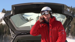 Man in ski gear talking on cell phone near back of car Stock Footage