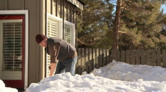 Man shoveling snow on front deck of home Stock Footage