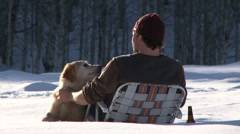 Man sitting in lawn chair out in the snow with golden retriever and a beer - stock footage