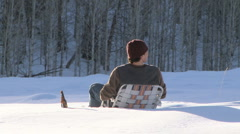 Couple embraces in a lawn chair out in the snow with golden retriever close by - stock footage