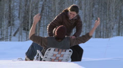 Couple embraces in a lawn chair out in the snow - stock footage