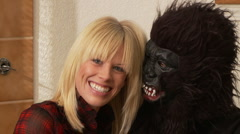 Woman kisses man in a gorilla mask near Christmas tree - stock footage