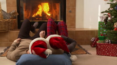 Couple in Santa Claus hats laying in front of the fireplace Stock Footage