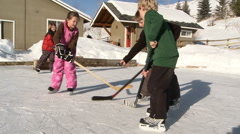 Four young kids play hockey on backyard ice rink - stock footage
