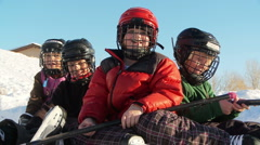 Four young kids pose in hockey gear on backyard ice rink - stock footage