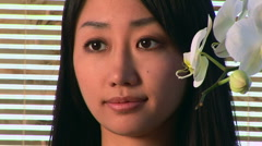 Portrait of young Asian woman face with orchid Stock Footage