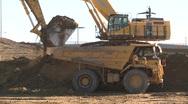 Construction, Cat 773e dump truck, #3 and big backhoe loads profile. Stock Footage