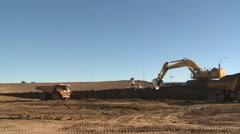 Construction, Cat 773e dump truck, #4 and big backhoe loads wide shot Stock Footage