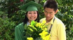 Young Asian woman in graduation gown with boyfriend outside - stock footage