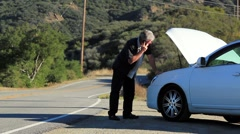 MANS CAR BREAKS DOWN ON ROAD - stock footage