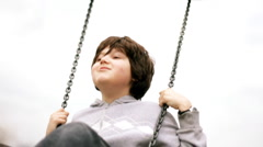 Young boy on a swing, slow motion, shot at 60fps Stock Footage