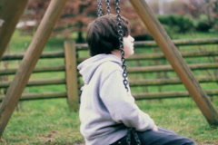 Stock Video Footage of Young, sad, lonely boy on a swing, dolly shot