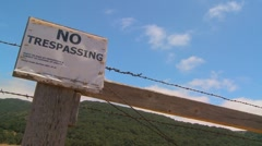 Time lapse of clouds drifting past a no trespassing sign. - stock footage