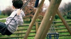 Young boy on a swing, dolly shot Stock Footage