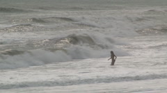 Girl wades into heavy surf Stock Footage