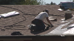 Roofing contractor carefully aligns shingles Stock Footage