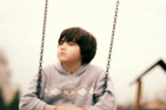 Young, sad, lonely boy on a swing, dolly shot Stock Footage