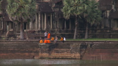 A couple of Buddhist monks in orange ropes in front of Angkor Wat - stock footage