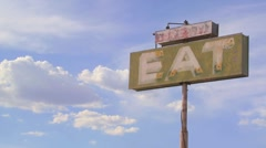Time lapse shot of clouds drifting past a sign saying eat. - stock footage