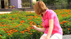 Young girl looking at marigold flowers Stock Footage